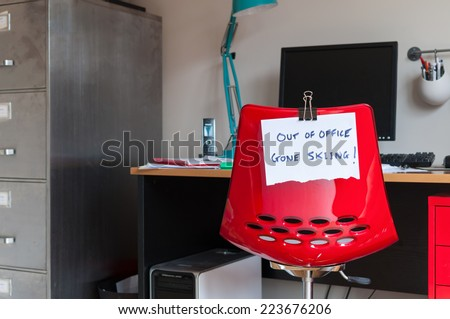 Employee leaves note on back of office chair: Out of Office. Gone Skiing! - stock photo