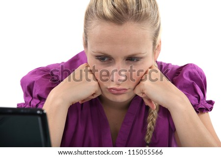 Employee pouting in front of her computer - stock photo