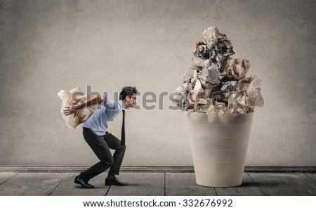 Employee trowing a piece of paper in a giant bin - stock photo