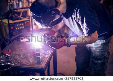 Employee welding aluminum using TIG welder in workshop. - stock photo