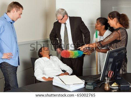 Employees having caught a colleague sleeping at his desk - stock photo