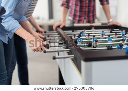 Employees Playing Table Soccer Indoor Game in the Office During Break Time to Relieve Stress from Work. - stock photo
