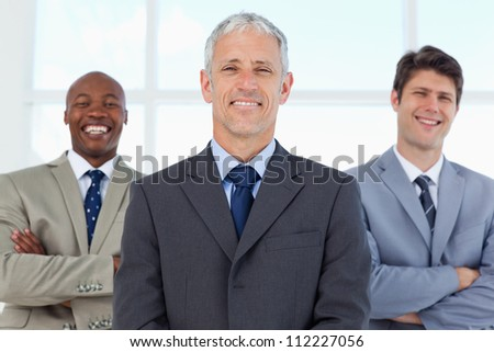 Employees standing in the back while laughing and being led by their mature manager - stock photo