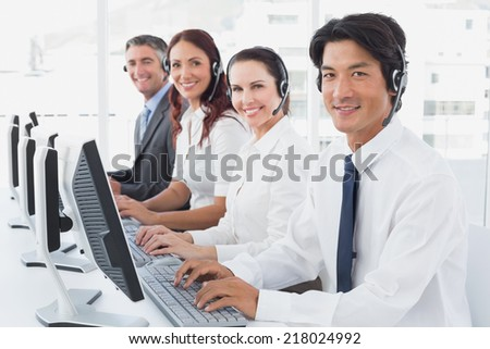 Employees typing on their computers using headsets - stock photo