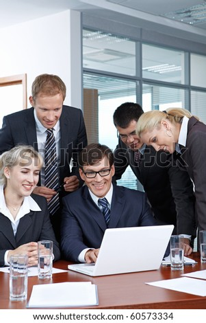 Employees with the boss looking at laptop monitor