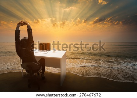 Employees work during rest and relaxation Imagine him sitting in the office. At the beach in the morning. - stock photo