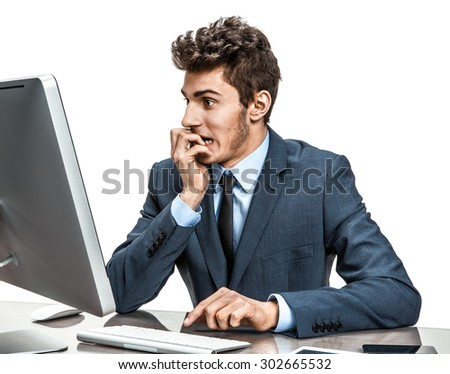 Employer looking at computer screen with horror / modern businessman at the workplace working with computer, depression and crisis concept - stock photo