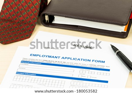 Employment application form with resume, pen, neck tie, and notebook - stock photo