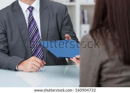 Employment interview with a close up view of a female applicant handing over a file containing her curriculum vitae to the businessman conducting the interview - stock photo