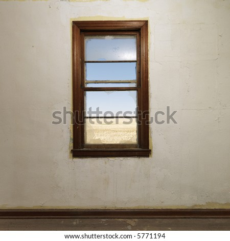 Empty abandoned room with widow centered on wall. - stock photo
