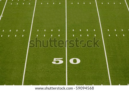 Empty American football field showing 50 yard line. - stock photo