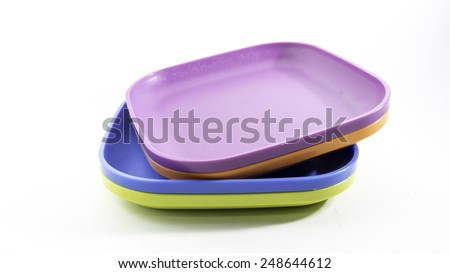 Empty and colourful luncheon plastic square luncheon food plates. Isolated on white background. Copy space.
