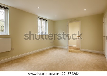 Empty apartment bedroom with twin windows radiator and closet