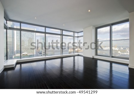 empty apartment with hard wood floor an floor to ceiling windows - stock photo