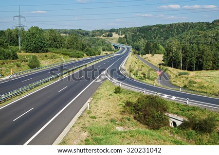 Empty asphalt highway with the slip road and traffic sign give way. Wooded landscape. Drain channel beneath the road. Electronic toll gate in the distance. View from above. Sunny day with blue skies. - stock photo