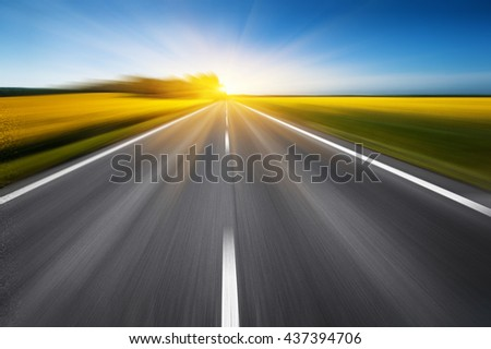 empty asphalt road and floral field of yellow flowers with blur in motion. abstract nature background - stock photo