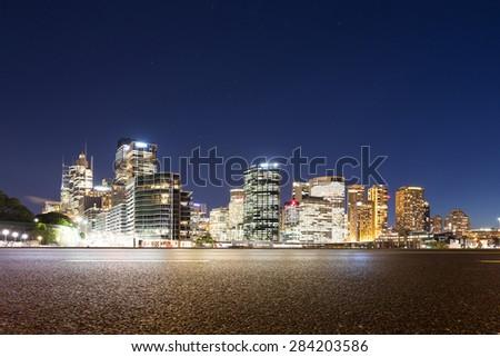 Empty asphalt road and illuminated modern cityscape background at night - stock photo