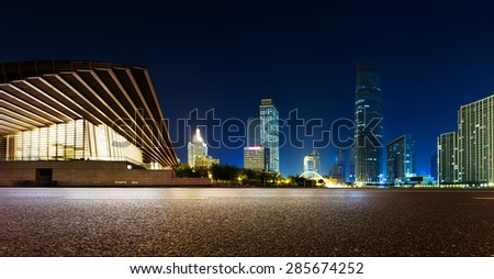 Empty asphalt road and modern skyline at night - stock photo