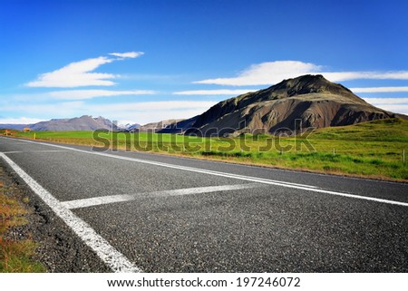 Empty asphalt road in Iceland on a sunny summery day with a mountain in background