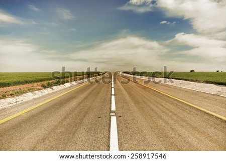Empty asphalt road through green fields aspiring to horizon. Image done with warm toned effect - stock photo