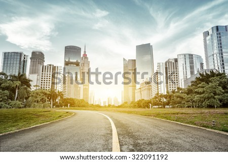 empty asphalt road with trees aside and skyscrapers under sunbeam - stock photo