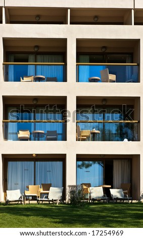 Empty balconies with chairs and tables at Greek hotel - stock photo