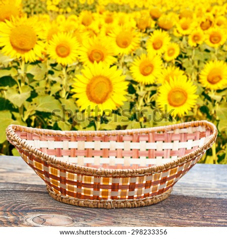 Empty basket on old wooden table.In the background blurred field of sunflowers - stock photo
