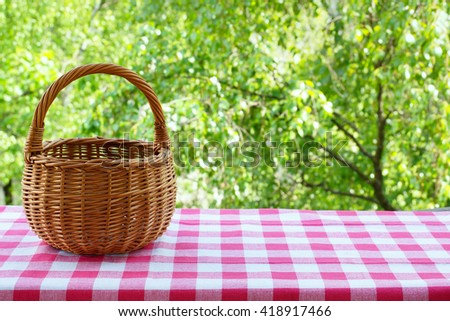 Empty basket on the table with checkered table cloth on a background of green trees.