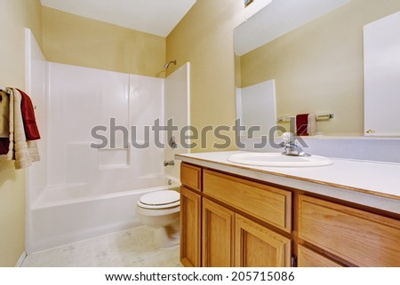 Empty bathroom interior in soft ivory with white bath tub and honey bathroom vanity cabinet