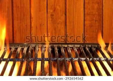 Empty BBQ Flaming Charcoal Cast Iron Grill  Close-up And Rustic Wood Wall In The Background. - stock photo