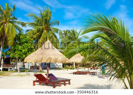 Empty beach bed under thatched umbrellas on a sandy beach
