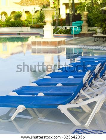 Empty beach chairs near  pool - stock photo