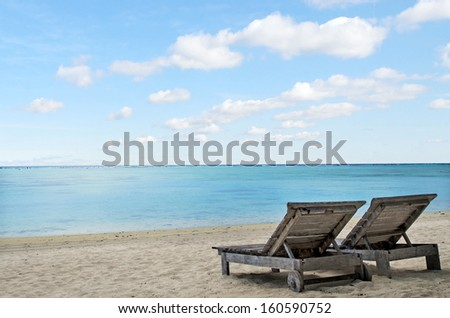 Empty beach chairs on empty tropical beach in  Aitutaki Lagoon Cook Islands