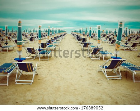 Empty beach scenery with deckchairs and umbrellas. Retro style.