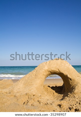 Empty beach with castle made of golden sand in the foreground - stock photo