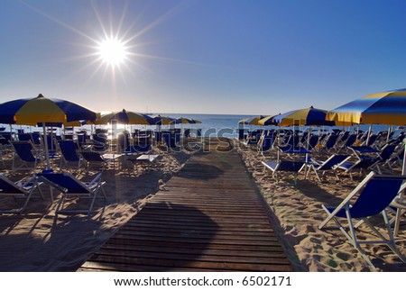 Empty beach with umbrellas and sun shortly after the sunrise - stock photo