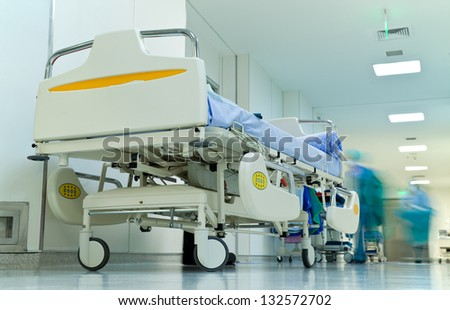Empty bed in busy hospital corridor, blurred figures with medical uniform working - stock photo