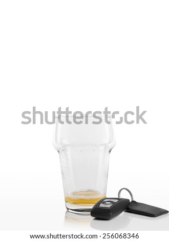 Empty beer glass next to car keys on a white background - stock photo