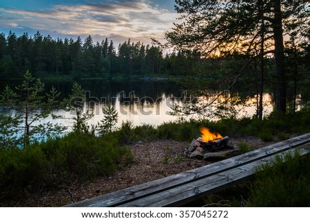 Empty bench at the camp fire in the Swedish forrest, view over the lake. - stock photo