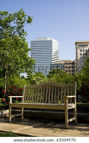 Empty Bench in the City An empty bench sits in a downtown park. Vertical. - stock photo