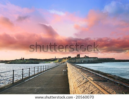 Empty Bench on Tynemouth Pier leading to Castle on cliffside as the Sunsets in November, Wide angle capture