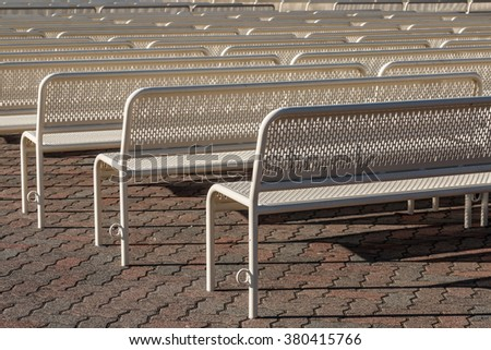Empty benches in rows from behind facing left. - stock photo