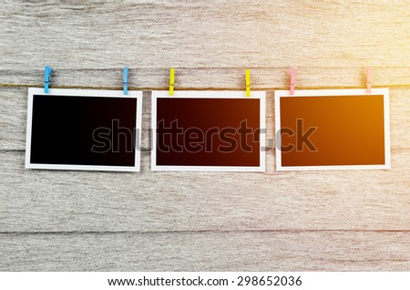 empty black photo frames hanging with clothespins on wooden background in vintage tone - stock photo