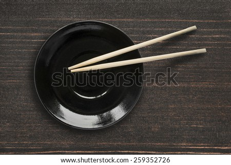 Empty black plate and wooden chopsticks on wooden desk - stock photo