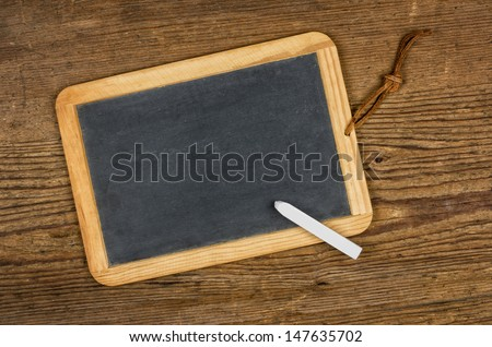 Empty blackboard with chalk on a wooden table - stock photo