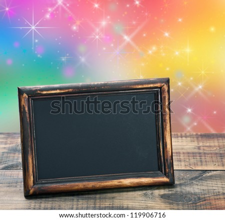 empty blackboard with wooden frame on a colored background