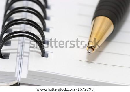 Empty blank ring, spiral notepad, gold pen closeup - stock photo