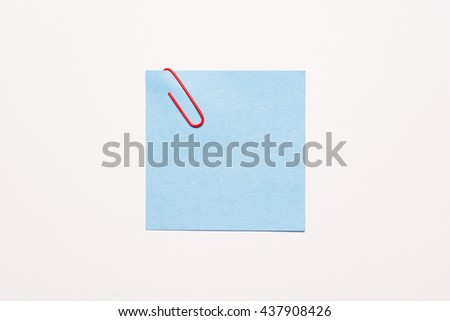 Empty blue notepaper with red paper clip - stock photo