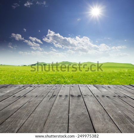 Empty board with meadow and sunny sky background - stock photo