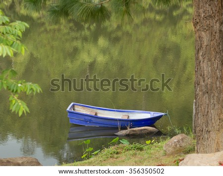Empty boat in the calm water of a pond or lake in autumn. - stock photo